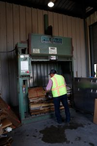 Man standing at a corrugated cardboard bailer.